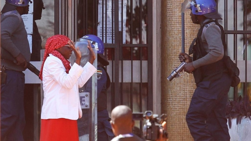 A woman lifts her hands as police confront protestors during a demonstration in Harare, Friday, Aug. 26, 2016.  The demonstration organised by opposition political parties calling for reforms is the first time that the fractured opposition has joined forces in a single unified action to confront President Robert Mugabes government.(AP Photo/Tsvangirayi Mukwazhi)