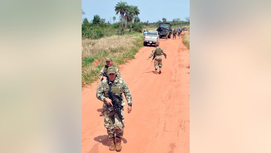 Members of the Paraguayan Army patrol near where suspected members of a little-known rebel group killed eight soldiers in Arroyito town, in northern Paraguay, Saturday, Aug. 27, 2016. Authorities suspect the attack was carried out by the Paraguayan People's Army. (AP Photo/Aldo Rojas)