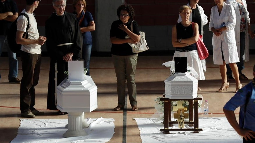 Coffins of some of the victims of Wednesday's earthquake lie inside a gymnasium in Ascoli Piceno, Italy, Friday, Aug. 26, 2016. Strong aftershocks rattled residents and rescue crews alike Friday as hopes began to dim that firefighters would find any more survivors from Italy's earthquake. The first funerals were scheduled for some of the victims, with the government declaring a day of national mourning and a state funeral scheduled for Saturday. (AP Photo/Gregorio Borgia)