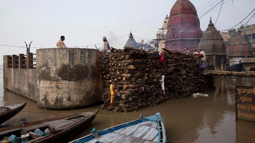 A thin line of smoke rises from burning funeral pyres on a rooftop of a temple at the flooded Manikarnika Ghat in Varanasi, India, Saturday, Aug. 27, 2016. As the mighty Ganges River overflowed its banks this past week following heavy monsoon rains, large parts of the Hindu holy town of Varanasi were submerged by floodwaters, keeping away thousands of Hindu devotees. Varanasi is a pilgrim town that Hindus visit to take a dip in the holy Ganges. (AP Photo/Tsering Topgyal)