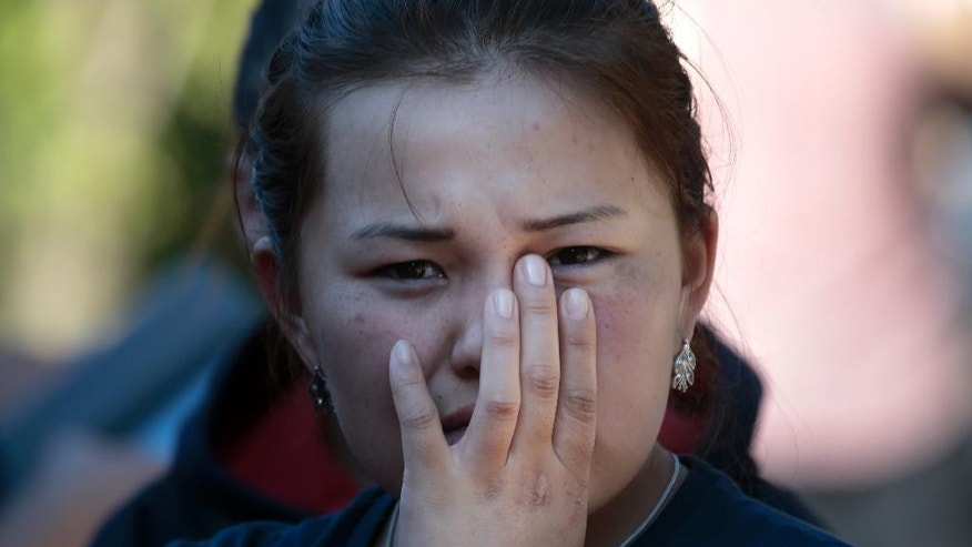 A woman reacts as colleagues and relatives of dead workers from Kyrgyzstan gather next to the burnt building of a printing plant's warehouse in Moscow, Russia, Saturday, Aug. 27, 2016. Russian emergency services say a fire swept through a printing plant's warehouse in Moscow on Saturday, killing 17 migrant workers from Kyrgyzstan. (AP Photo/Ivan Sekretarev)