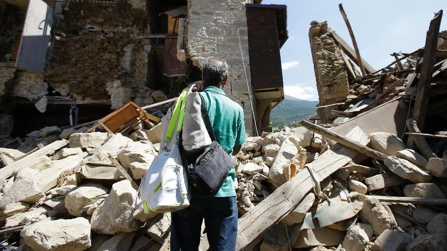 A man stands in front of his collapsed house after recovering his personal belongings, in Villa San Lorenzo, near Amatrice, central Italy, Saturday, Aug. 27, 2016 where a 6.1 earthquake struck just after 3:30 a.m., Wednesday. As Italians observed a day of national mourning, President Sergio Mattarella and Premier Matteo Renzi joined grieving family members for a state funeral for some of the victims of Wednesday's quake. (AP Photo/Antonio Calanni)