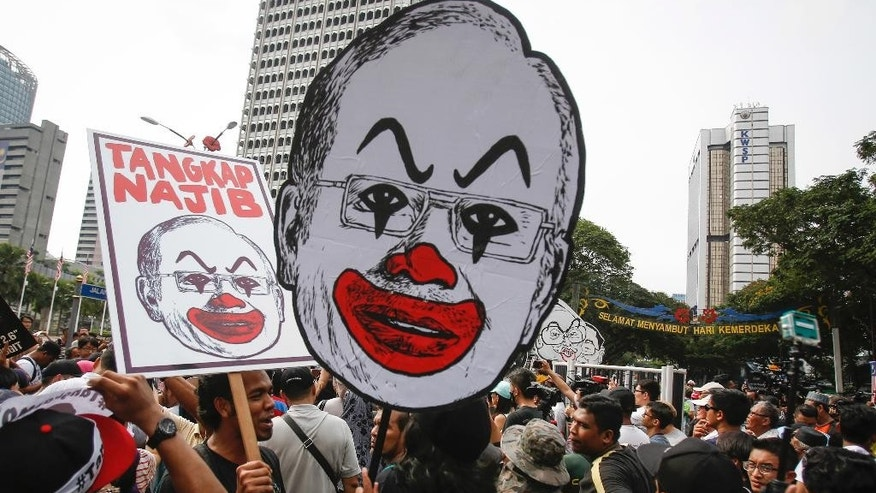"Student activists holds up a caricature of Malaysian Prime Minister Najib Razak during a rally calling for the arrest of ""Malaysian Official 1"" in Kuala Lumpur, Malaysia, Saturday, Aug. 27, 2016. Malaysian student activists have rallied to demand the arrest of Prime Minister Najib Razak, who has been implicated in a U.S. government probe into a massive fraud in a Malaysian investment fund. (AP Photo/Joshua Paul)"