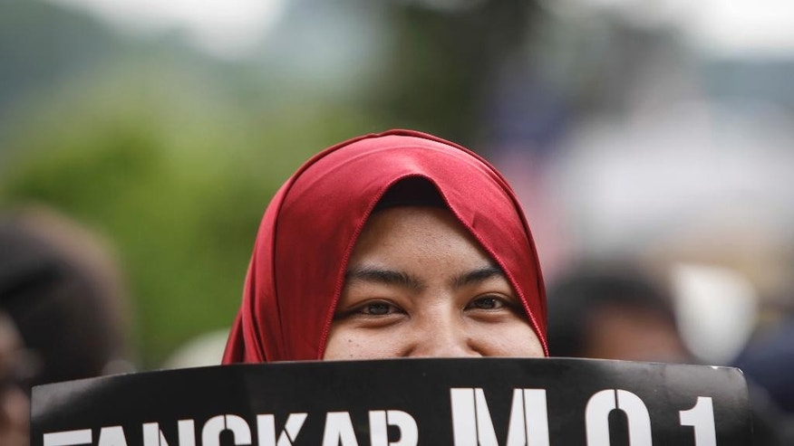 "A Malaysian Muslim woman holds up a placard translating ""Capture M.O.1"" during a rally calling for the arrest of Prime Minister Najib Razak in Kuala Lumpur Malaysia, Saturday, Aug. 27, 2016. Malaysian student activists have rallied to demand the arrest of Razak, who has been implicated in a U.S. government probe into a massive fraud in a Malaysian investment fund. (AP Photo/Joshua Paul)"