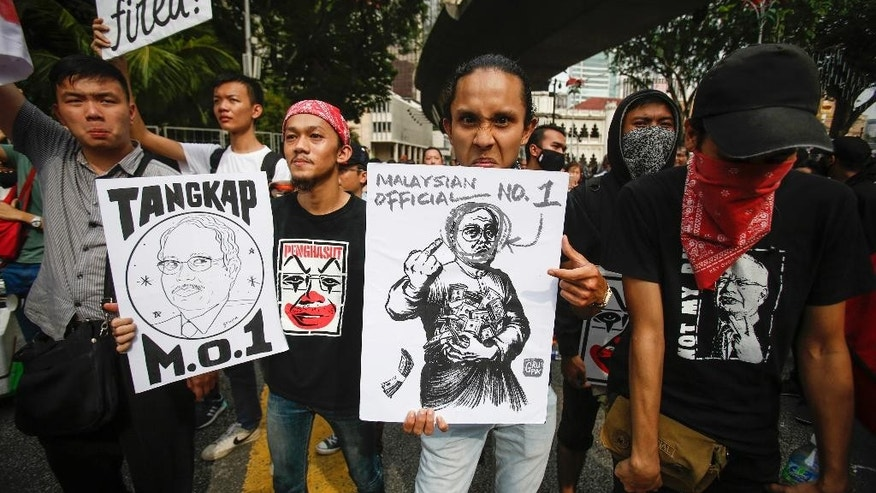 "Student activists holds up a caricatures of Malaysian Prime Minister Najib Razak during a rally calling for the arrest of ""Malaysian Official 1"" during a rally in Kuala Lumpur, Malaysia, Saturday, Aug. 27, 2016. Malaysian student activists have rallied to demand the arrest of Prime Minister Najib Razak, who has been implicated in a U.S. government probe into a massive fraud in a Malaysian investment fund. (AP Photo/Joshua Paul)"