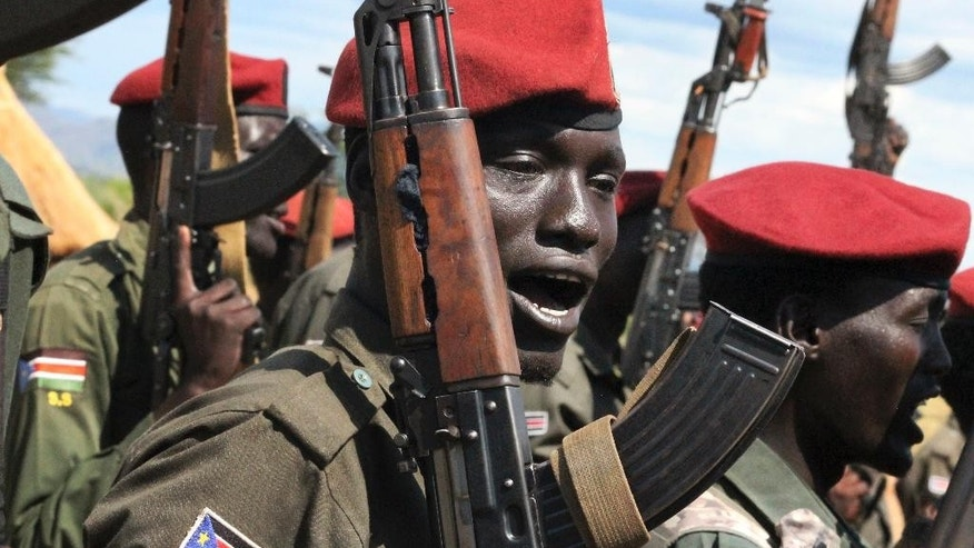 In this photo taken Thursday, April 14, 2016, government soldiers follow orders to raise their guns during a military parade in Juba, South Sudan. When South Sudan's president signed a peace deal a year ago to end the country's civil war he added 16 reservations to the agreement, which have now become a map of how it has unraveled. (AP Photo/Justin Lynch)