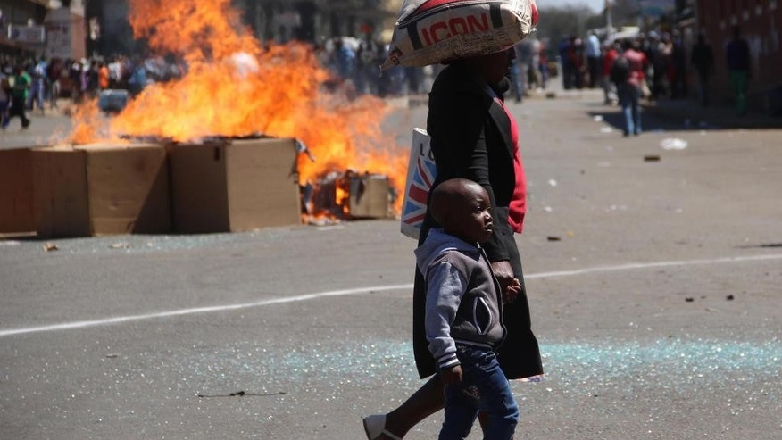 A woman and child pass a fire set alight during a protest in Harare, Friday, Aug. 26, 2016. The demonstration organised by opposition political parties calling for reforms, is the first time that the fractured opposition has joined forces in a single unified action to confront President Robert Mugabe's government. (AP Photo)