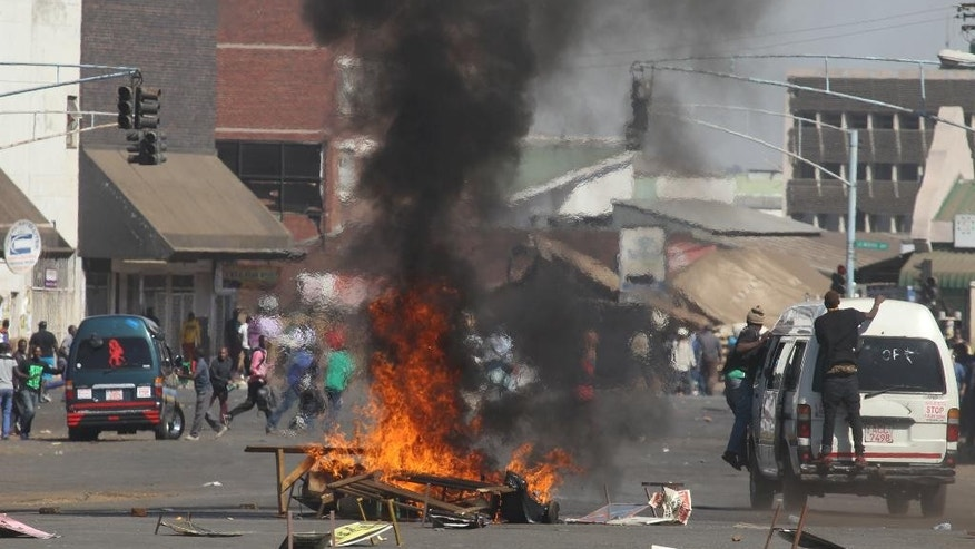 A fire burns in the street, set by protestors during a demonstration in Harare, Friday, Aug. 26, 2016.  The demonstration organised by a coalition of opposition political parties calling for political and social reforms was the first time that the fractured opposition has joined forces in a single unified action to confront President Robert Mugabes government. (AP Photo/Tsvangirayi Mukwazhi)