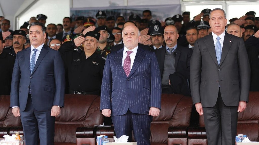 FILE -- In this Jan. 9, 2016 file photo, Iraqi Prime Minister Haider al-Abadi, center, then Defense Minister Khaled al-Obeidi, right, then Interior Minister Mohammed al-Ghabban, left, attend a ceremony marking Police Day, in Baghdad, Iraq. Recent political upheaval has left Iraq without a minister of defense or interior as the country prepares for the operation to retake Mosul -- expected to be the most complicated yet in the fight against the Islamic State group. Al-Obeidi was abruptly dismissed by a parliamentary no-confidence vote Thursday, Aug. 25, 2016, for reasons that seem to have little to do with his performance in office. Al-Ghabban submitted his resignation in early July amid mounting anger following a massive truck bombing claimed by IS that killed more than 300 people. (AP Photo/Karim Kadim, File)
