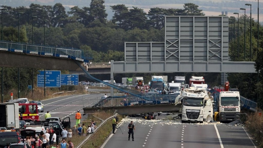 The scene on the London-bound M20 motorway, about 30 miles (48 kilometers) southeast of the capital, after a lorry hit a pedestrian bridge, causing it to collapse, Saturday Aug. 27, 2016. Witnesses and emergency services say a truck has struck an overpass and collapsed a pedestrian bridge onto one of England's busiest motorways, the M20, injuring one person. (Steve Parsons/PA via AP)