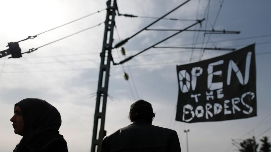FILE - In this Tuesday, March 22, 2016 file photo, migrants walk past a banner during a protest demanding the opening of the border between Greece and Macedonia, in the northern Greek border station of Idomeni, Greece. Faced with a flood of more than 1 million migrants across the Mediterranean in 2015, European nations tightened border controls, set up naval patrols to stop smugglers, negotiated an agreement with Turkey to limit the numbers crossing, shut the Balkan route used by hundreds of thousands, and tried to speed up deportations of rejected asylum-seekers. (AP Photo/Darko Vojinovic, File)