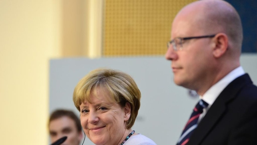 German Chancellor Angela Merkel, left,  smiles during a joint press conference with Czech Prime Minister Bohuslav Sobotka, right, in Prague, Czech Republic, Thursday, Aug. 25, 2016. (Roman Vondrous/CTK via AP)
