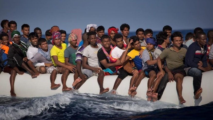Migrants and refugees fleeing Libya on board of a dinghy sail at the Mediterranean sea toward the Italian coasts, about 17 miles north of Sabratha, Libya, Sunday, Aug. 28, 2016. European nations have tightened border controls, shut down the Balkan route used by hundreds of thousands of people, negotiated an agreement with Turkey to curb new arrivals and taken other measures to curb the influx of migrants. But many problems still remain with Europe's uneven response to the crisis. (AP Photo/Emilio Morenatti)