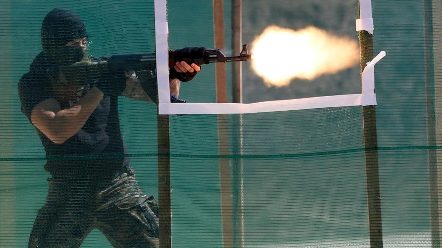 A supposed terrorist shoots during a joint anti-terrorist drill between Serbia and Republic of Srpska, not far from the border crossing Trbusnica, near the city of Loznica some 120 km (75 miles) west of Belgrade, Serbia, Sunday, Aug. 28, 2016. Anti-terrorist police from Serbia and the Serb mini-state in Bosnia have held a joint drill that could add to simmering tensions in the Balkans stemming from the 1990s' war. (AP Photo/Darko Vojinovic)