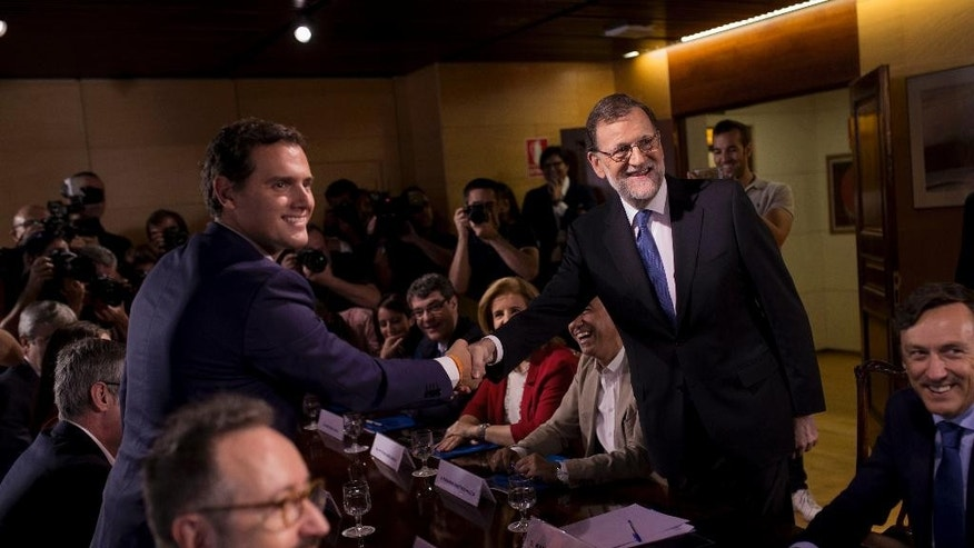 Spain's acting Prime Minster and Popular Party leader Mariano Rajoy, right, shakes hands with Ciudadanos party leader Albert Rivera during a meeting at the Spanish parliament in Madrid, Sunday, Aug. 28, 2016. Spanish conservative Popular Party has signed a deal with smaller, business-friendly Ciudadanos that could help avoid a possible third round of elections and possibly end the country's eight month political deadlock. (AP Photo/Francisco Seco)