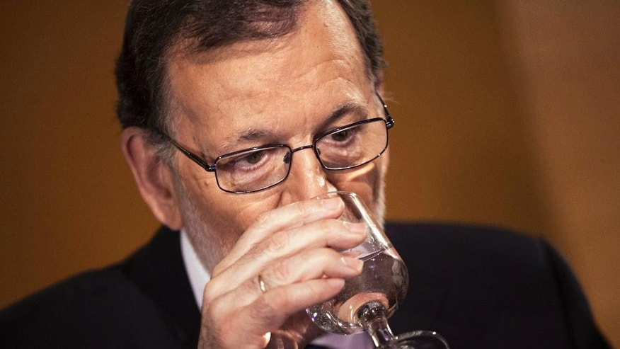 Spain's acting Prime Minister and Popular Party leader Mariano Rajoy drinks a glass of water during a meeting with Ciudadanos party leader Albert Rivera at the Spanish parliament in Madrid, Sunday, Aug. 28, 2016. Spanish conservative Popular Party has signed a deal with smaller, business-friendly Ciudadanos that could help avoid a possible third round of elections and possibly end the country's eight month political deadlock. (AP Photo/Francisco Seco)
