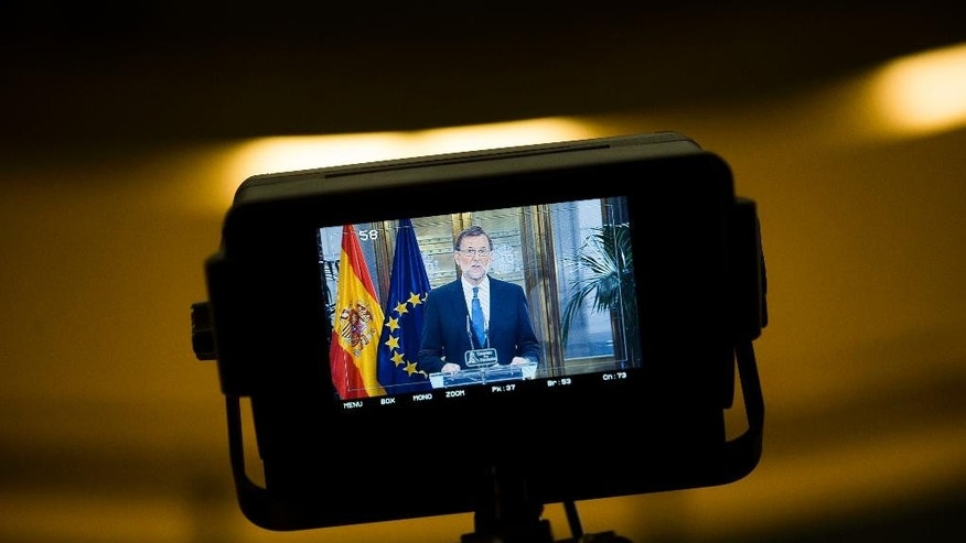 Spain's acting Prime Minister and Popular Party leader Mariano Rajoy is shown in a tv camera screen as he talks to journalists during a news conference following a meeting with Ciudadanos party leader Albert Rivera at the Spanish parliament in Madrid, Sunday, Aug. 28, 2016. Spanish conservative Popular Party has signed a deal with smaller, business-friendly Ciudadanos that could help avoid a possible third round of elections and possibly end the country's eight month political deadlock. (AP Photo/Francisco Seco)
