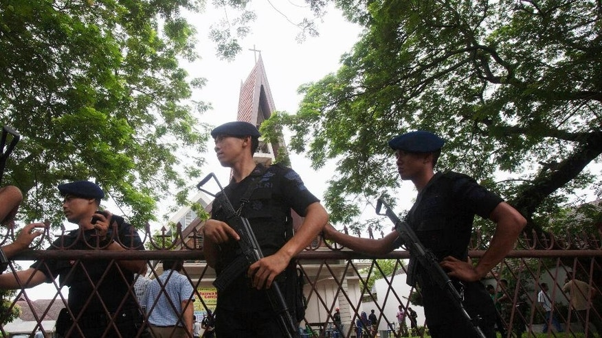 Indonesian police officers guard a church compound following an attack during Sunday Mass in Medan, North Sumatra, Indonesia, Sunday, Aug. 28, 2016. Police in the western Indonesian city said a would-be suicide bomber failed to detonate explosives in the packed church. (AP Photo/Binsar Bakkara)