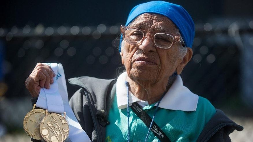Man Kaur, 100, of India, holds the gold medals she won in shot put and javelin events before competing in the 100-meter track and field event at the Americas Masters Games in Vancouver, British Columbia, Monday, Aug. 29, 2016. More than 10,000 athletes aged 30 and older are participating in the games which continue until Sept. 4. (Darryl Dyck/The Canadian Press via AP)