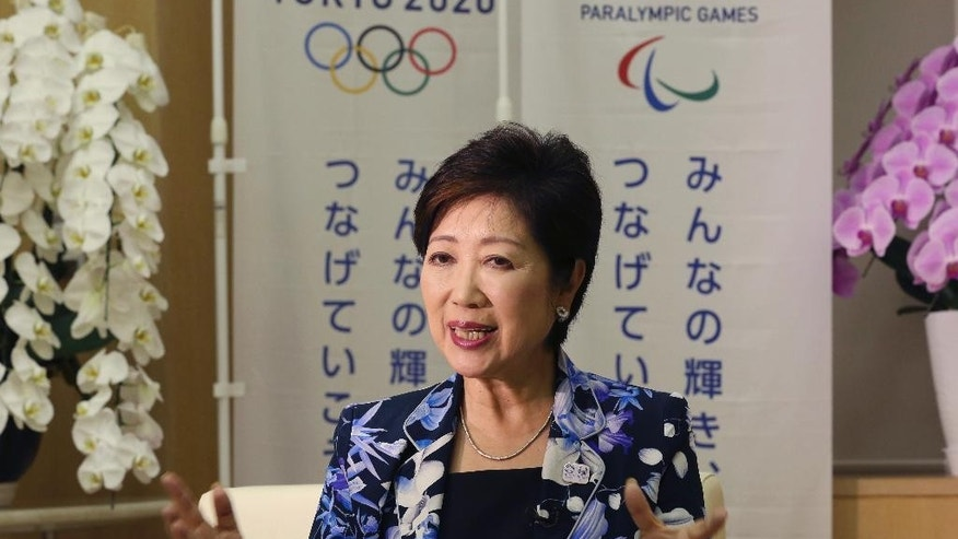 "Tokyo Governor Yuriko Koike speaks during an interview with The Associated Press at her office in Tokyo, Monday, Aug. 29, 2016. Tokyo's first female leader says she will use her platform to host a cost-efficient and environmentally friendly 2020 Olympics and push a women's rights agenda that she hopes will be a model for Japan's central government. ""Unity in Diversity,"" a slogan for the 2020 Olympics, is written on the banners. (AP Photo/Koji Sasahara)"