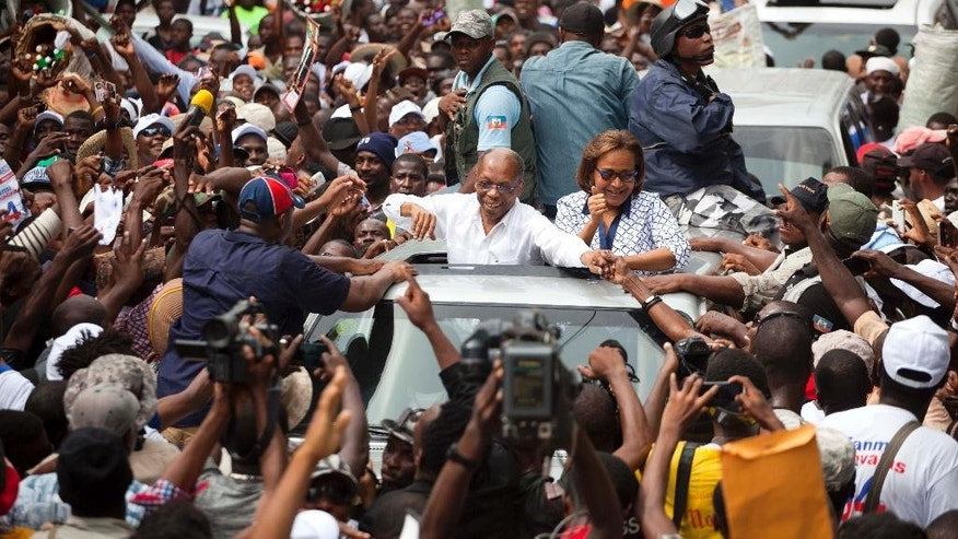 Haiti's former President Jean-Bertrand Aristide waves to supporters as he campaigns with presidential candidate Maryse Narcisse of the Fanmi Lavalas political party, in Petion-Ville, Haiti, Monday, Aug. 29, 2016. The twice-ousted Haitian leader made the rare public appearance to support Narcisse, the candidate of the political faction he founded decades ago. A presidential redo election is scheduled for Oct. 9. (AP Photo/Dieu Nalio Chery)