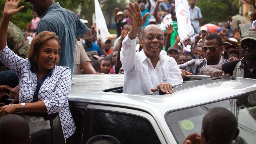 Haiti's former President Jean-Bertrand Aristide, center, waves to supporters as he campaigns with presidential candidate Maryse Narcisse, left, of the Fanmi Lavalas political party, in Petion-Ville, Haiti, Monday, Aug. 29, 2016. The twice-ousted Haitian leader made the rare public appearance to support Narcisse, the candidate of the political faction he founded decades ago. A presidential redo election is scheduled for Oct. 9. (AP Photo/Dieu Nalio Chery)