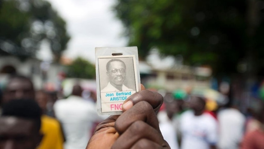 A supporter of Haiti's former President Jean-Bertrand Aristide and presidential candidate Maryse Narcisse, of the Fanmi Lavalas political party, holds up a picture of Jean Bertrand Aristide in Petion-Ville, Haiti, Monday, Aug. 29, 2016. The twice-ousted Haitian leader made the rare public appearance to support Narcisse, the candidate of the political faction he founded decades ago. A presidential redo election is scheduled for Oct. 9. (AP Photo/Dieu Nalio Chery)