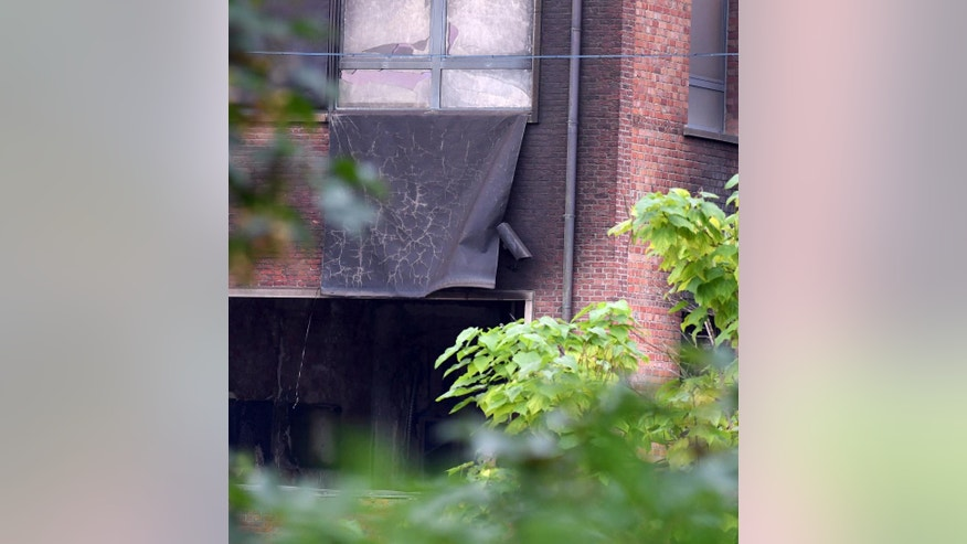 Damage can be seen at the building of the National Criminology Lab in Brussels on Monday, Aug. 29, 2016. Belgian media initially reported an explosion rocked the building in the early hours of Monday. However, the Brussels prosecutor's office later described the incident as much more likely an arson attack designed to destroy criminal evidence and spokeswoman Ine Van Wymersch said any sounds of an explosion heard by residents may have been caused by material being consumed in the fire. (AP Photo/Geert Vanden Wijngaert)