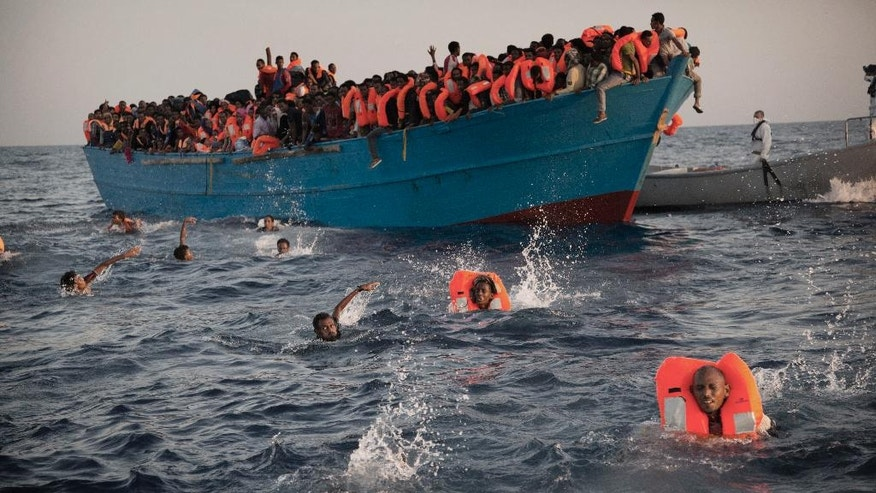 Migrants, most of them from Eritrea, jump into the water from a crowded wooden boat as they are helped by members of an NGO during a rescue operation at the Mediterranean sea, about 13 miles north of Sabratha, Libya, Monday, Aug. 29, 2016. Thousands of migrants and refugees were rescued Monday morning from more than 20 boats by members of Proactiva Open Arms NGO before transferring them to the Italian cost guards and others NGO vessels operating at the zone.(AP Photo/Emilio Morenatti)