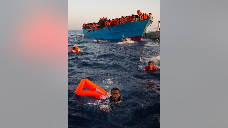Migrants, most of them from Eritrea, jump into the water from a crowded wooden boat as they are helped by members of an NGO during a rescue operation at the Mediterranean sea, about 13 miles north of Sabratha, Libya, Monday, Aug. 29, 2016. Thousands of migrants and refugees were rescued Monday morning from more than 20 boats by members of Proactiva Open Arms NGO before transferring them to the Italian cost guards and others NGO vessels operating at the zone. (AP Photo/Emilio Morenatti)