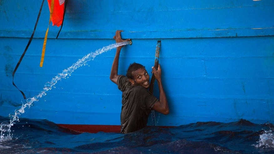 A man holds himself on the side of  a boat after jumping into the sea from a crowded wooden boat during a rescue operation at the Mediterranean sea, about 13 miles north of Sabratha, Libya, Monday, Aug. 29, 2016. Thousands of migrants and refugees were rescued Monday morning from more than 20 boats by members of Proactiva Open Arms NGO before transferring them to the Italian cost guards and others NGO vessels operating at the zone.(AP Photo/Emilio Morenatti)