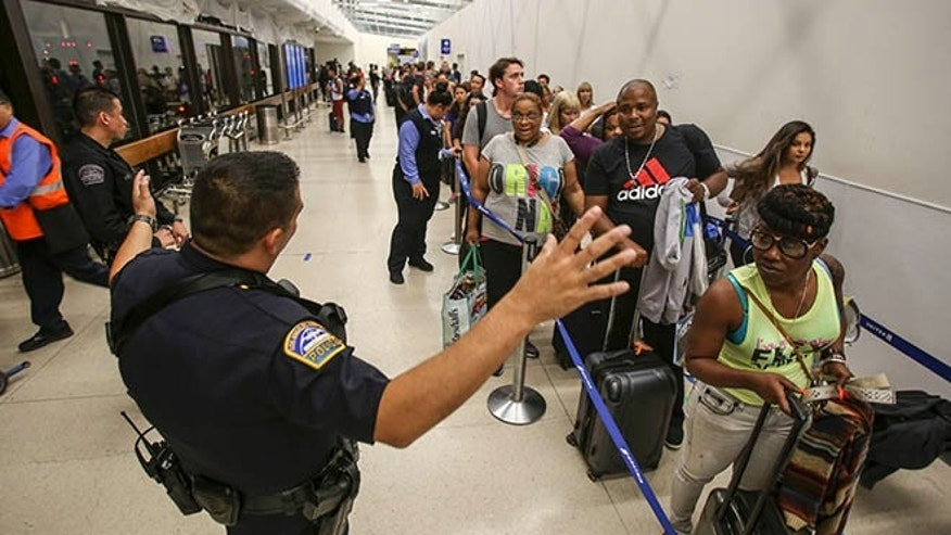 Police officers stand guard as passengers wait in line at Terminal 7 in Los Angeles International Airport, Sunday, Aug. 28, 2016.