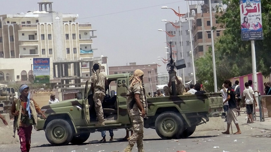 Soldiers and onlookers at the site of the suicide attack in Aden.