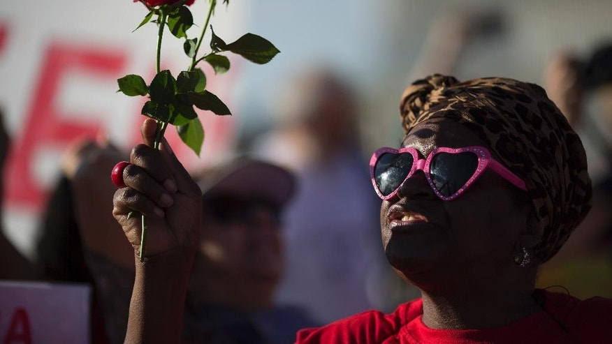 A demonstrator in support of Brazil's suspended President Dilma Rousseff holds up two red roses in front of the National Congress where Rousseff's impeachment trial is taking place, in Brasilia, Brazil, Monday, Aug. 29, 2016. Fighting to save her job, Rousseff told senators on Monday that the allegations against her have no merit. Rousseff's address comes on the fourth day of the trial. (AP Photo/Leo Correa)