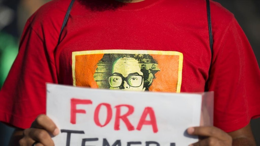 """A demonstrator, wearing a T shirt with an image depicting Brazil's suspeneded President Dilma Rousseff, in front of the National Congress where her impeachment trial is taking place, in Brasilia, Brazil, Monday, Aug. 29, 2016. Fighting to save her job, Rousseff told senators on Monday that the allegations against her have no merit. Rousseff's address comes on the fourth day of the trial. The demonstrator holds a sign that reads in Portuguese; """"Out Temer,"""" in reference to acting President Michel Temer. (AP Photo/Leo Correa)"""