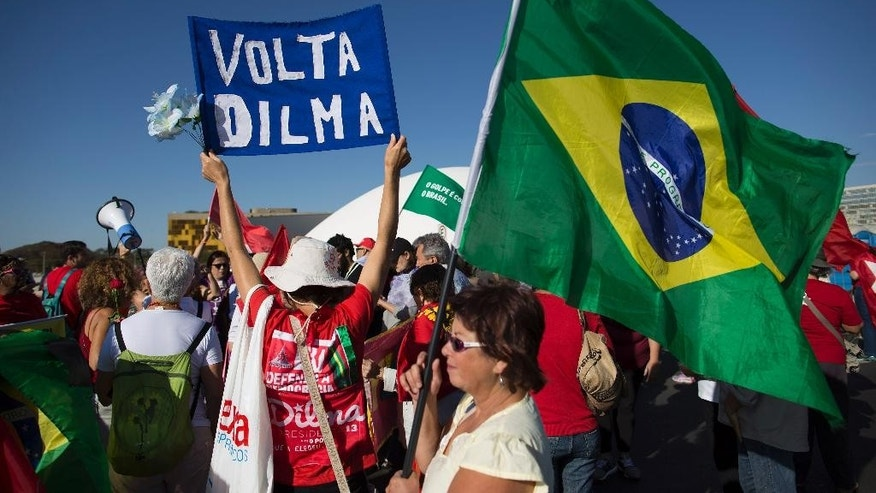 "A demonstrator holds up a banner with a message that reads in Portuguese; ""Dilma come back"" in front of the National Congress where the impeachment trial of Brazil's suspended President Dilma Rousseff is taking place, in Brasilia, Brazil, Monday, Aug. 29, 2016. Fighting to save her job, Rousseff told senators on Monday that the allegations against her have no merit. Rousseff's address comes on the fourth day of the trial. (AP Photo/Leo Correa)"