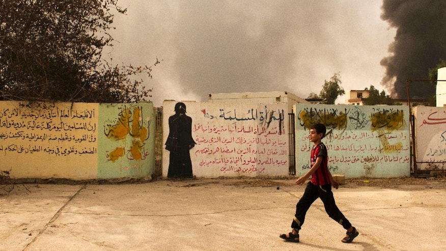 In this Sunday, August 28, 2016 photo, a young boy walks past partially defaced Islamic State group instructions for muslim women and a written warning to violators of the militant's extremist interpretation of Islam in Qayara, Iraq. The skies above Qayara are black with the smoke from more than a dozen oil wells set alight by Islamic State group fighters attempting to obstruct airstrikes as Iraqi forces pushed into the the town on bank of the Tigris last week and took control of the entire area Thursday. (AP Photo/Susannah George)