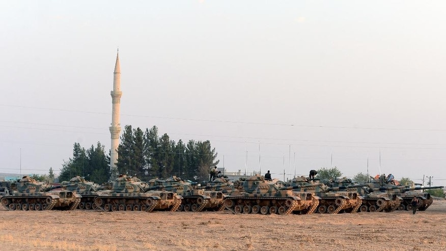 Turkish tanks stationed near the Syrian border, in Karkamis, Turkey, Saturday, Aug. 27, 2016. Turkey on Wednesday sent tanks across the border to help Syrian rebels retake the key Islamic State-held town of Jarablus and to contain the expansion of Syria's Kurds in an area bordering Turkey.(Ismail Coskun, IHA via AP)