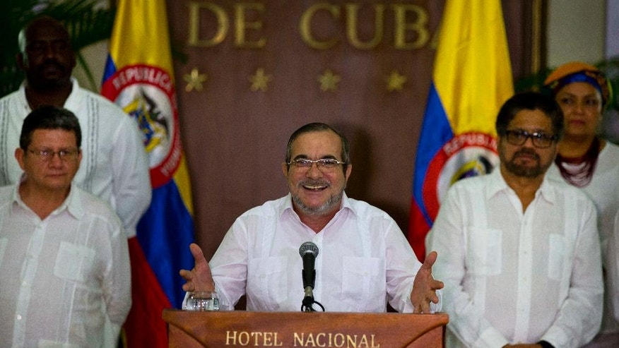 Commander of the Revolutionary Armed Forces of Colombia or FARC, Rodrigo Londono, better known as Timochenko or Timoleon Jimenez talks to the press, accompanied by Ivan Marquez, right, chief negotiator of the Revolutionary Armed Forces of Colombia and Pablo Catatumbo, left, chief of the FARC's western bloc, in Havana, Cuba, Sunday, August 28, 2016. The commander of Colombia's biggest rebel movement says its fighters will permanently cease hostilities with the government beginning with the first minute of Monday, as a result of their peace accord for ending five decades of war. (AP Photo/Ramon Espinosa)