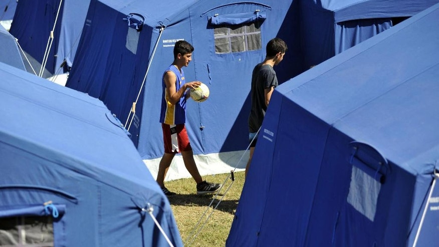 Boys walk in the tent camp that was set in Arquata Del Tronto, central Italy, Monday, Aug. 29, 2016. With thousands left homeless after Italy's earthquake, authorities are debating how to provide warmer, sturdier housing for them besides the rows of emergency blue tents set up in the Apennine Mountains, where even summer nights can get chilly. (Cristiano Chiodi/ANSA via AP)