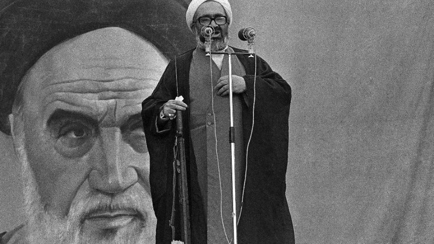 FILE -- In this November 23, 1979 file photo, then President of Iran's Ruling Revolutionary Council, Ayatollah Hossein Ali Montazeri holds a rifle as he addresses a large rally at Tehran University. In August, 2016, a website run in Montazeri's honor by his family released a tape recording of Montazeri that has rekindled memories of the Islamic Republic's mass execution of prisoners in 1988. The tape appears to have Montazeri, who at one time was in line to become Iran's supreme leader, criticizing the executions. Rights groups suggest as many as 5,000 people were executed in 1988. (AP Photo, File)