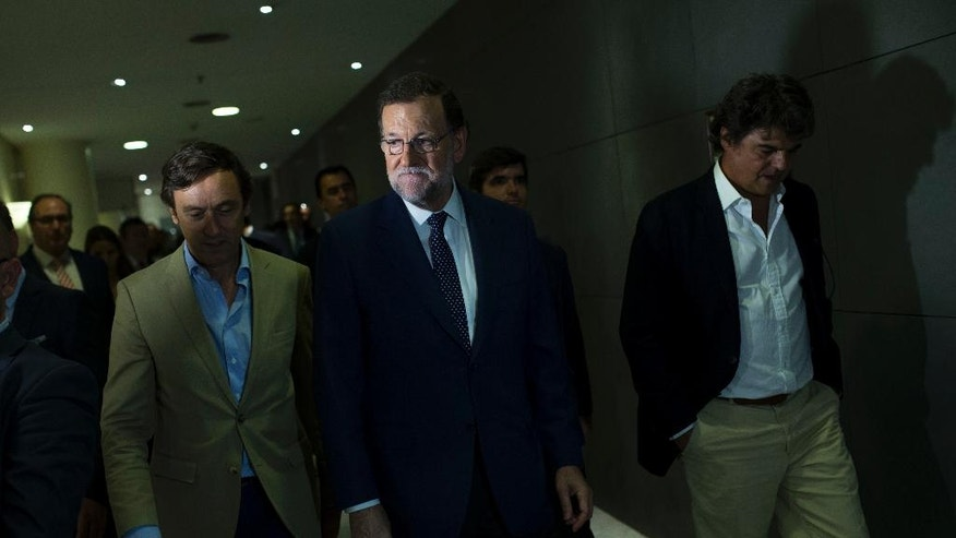 Spain's acting Prime Minister and Popular Party leader Mariano Rajoy, centre, leaves after his meeting with Socialists Party leader Pedro Sanchez at the Spanish parliament in Madrid, Monday, Aug. 29, 2016. Rajoy met with Sanchez in a last-ditch effort to convince him not to scupper the premier's bid to form a government this week and end the country's eight-month political impasse following two inconclusive elections. (AP Photo/Francisco Seco)