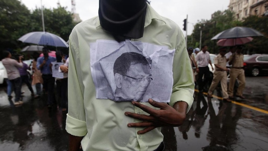 FILE - In this June 13, 2011, Indian journalists hold a photo of Jay Dey, a well-known investigative journalist who was gunned down Saturday by assailants, as they march to protest his killing in Mumbai. The Committee to Protect Journalists counted 27 journalists killed for their work since 1992, and noted it was still investigating more than two dozen cases to determine if those journalists' deaths were also work related. (AP Photo/Rajanish Kakade, File)