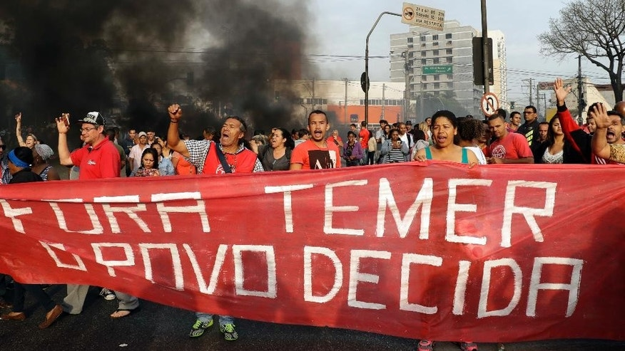 "Demonstrators hold a banner that reads in Portuguese; ""Temer out, the people decide"" during a protest against Brazil's acting President Michel Temer, in Sao Paulo, Brazil, Tuesday, Aug. 30, 2016. Suspended President Dilma Rousseff mounted a forceful defense at her impeachment trial Monday, blasting her critics ahead of a Senate vote that could come Tuesday on whether to remove her from office permanently. (AP Photo/Andre Penner)"