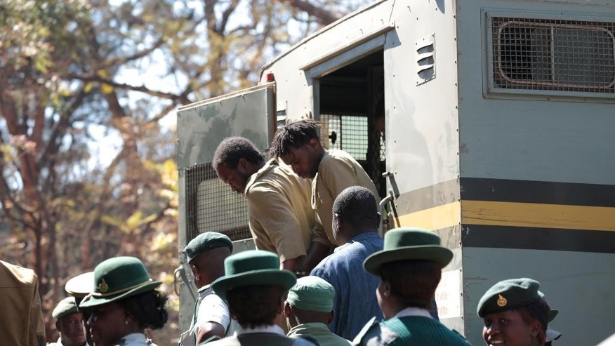 Some of the suspected demonstrators make a court appearance in Harare, Monday, Aug. 29, 2016. 67 suspected demonstrators made a court appearance following their arrests on Friday during protests called by opposition political parties who were advocating for reforms in the Southern African nation. The protests were the first time that the fractured opposition has joined hands in a single unified action to confront President Robert Mugabe's government since 2007. (AP Photo/Tsvangirayi Mukwazhi)