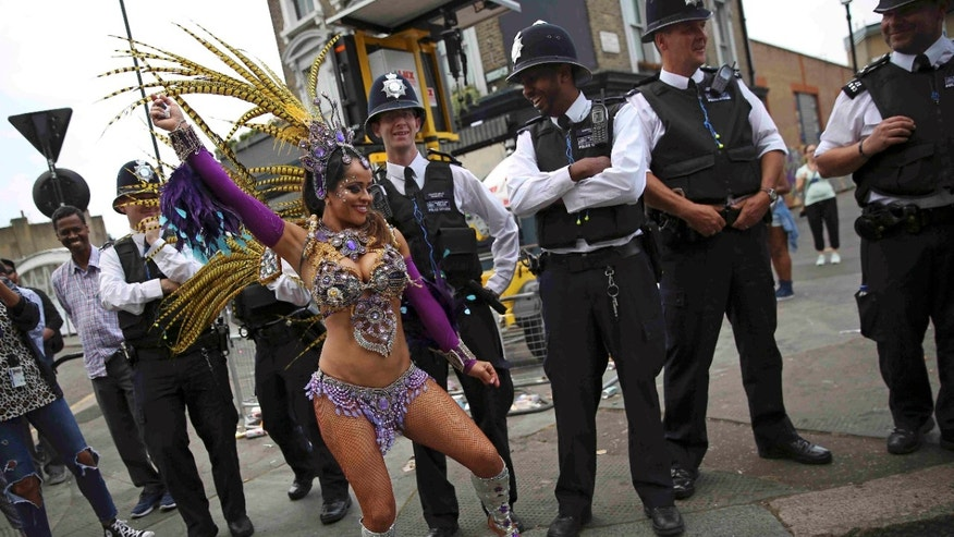 Police look as a performer dances during the Notting Hill Carnival in London on Monday.