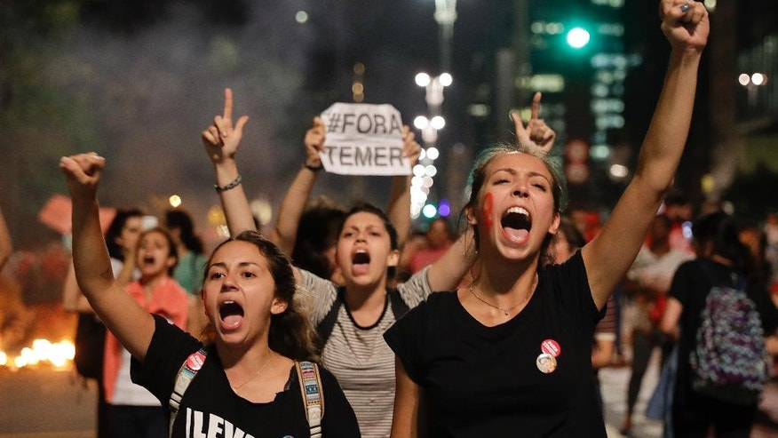 Demonstrators shout slogans against acting Brazil's President Michel Temer during a rally in support of Brazil's suspended President Dilma Rousseff in Sao Paulo, Brazil, Monday, Aug. 29, 2016. Police fired tear gas against the demonstrators. Fighting to save her job, Rousseff appeared before congress for her impeachment trial, to defend herself as her accusers say she hurt the economy with budget manipulations. (AP Photo/Andre Penner)