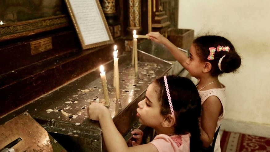 Egyptian Christian girls light candles in the Hanging Church in Old Cairo, Egypt, Tuesday, Aug. 30, 2016. After long hoping for an end to restrictions on the building of churches, many of Egypt's Christians are infuriated and feeling betrayed after lawmakers on Tuesday passed a law giving authorities broad powers to veto construction for vague reasons including worries over 'national security.' (AP Photo/Nariman El-Mofty)