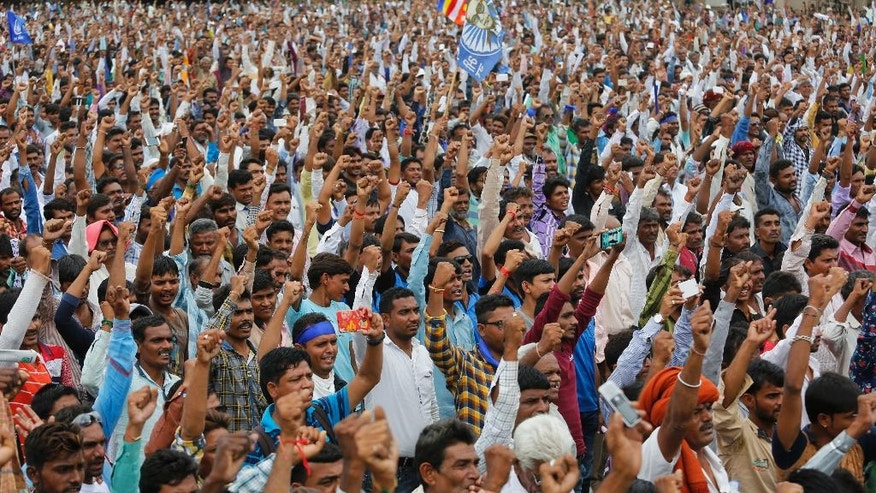"""FILE- In this Aug. 15, 2016 file photo, hundreds of members of India's low-caste Dalit community gather for a rally in Una, Gujarat state, India as they protest after four men belonging to the Dalit community were beaten while trying to skin a dead cow in western India. The brutal beating of four men from the lowest rung of India's caste hierarchy, attacked for skinning a dead cow, has highlighted the persisting power of caste, 65 years after caste prejudice was banned in India. Dalits _ as """"untouchables"""" are now called _ are increasingly signaling that they will no longer tolerate such bigotry, with an emerging class of educated and empowered young Dalits refusing to be cowed by the centuries-old discrimination, triggering deadly violence. (AP Photo/Ajit Solanki, File)"""
