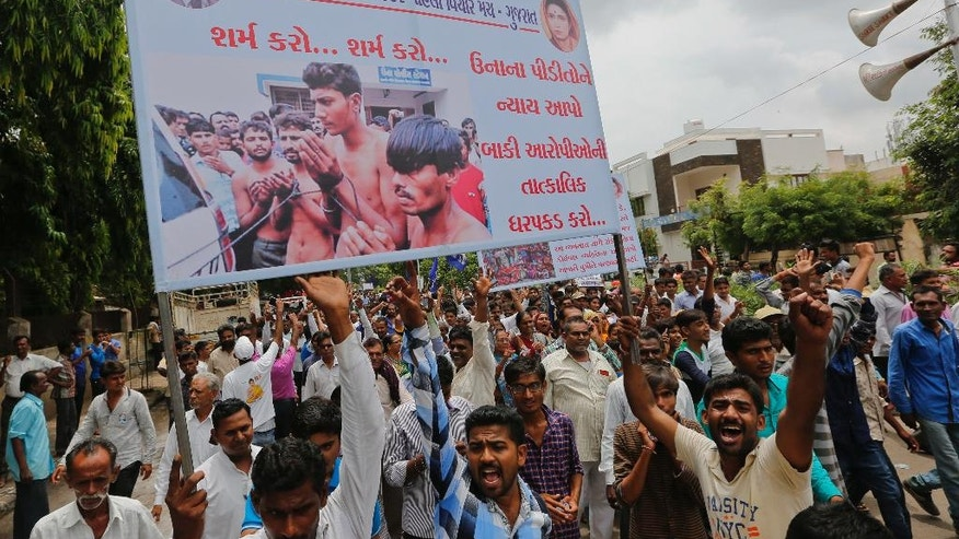 """FILE- In this July 31, 2016 file photo, members of India's low-caste Dalit community hold a banner with a photograph showing four men belonging to their community who were beaten while trying to skin a dead cow as they gather for a rally in Ahmadabad, India. The banner in Gujarati reads """"shame shame, Give justice to Una victims, immediately arrest rest accused"""". The brutal beating of four men from the lowest rung of India's caste hierarchy, attacked for skinning a dead cow, has highlighted the persisting power of caste, 65 years after caste prejudice was banned in India. Dalits _ as """"untouchables"""" are now called _ are increasingly signaling that they will no longer tolerate such bigotry, with an emerging class of educated and empowered young Dalits refusing to be cowed by the centuries-old discrimination, triggering deadly violence. (AP Photo/Ajit Solanki, File)"""